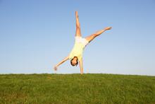 Young Woman Cartwheels In Field