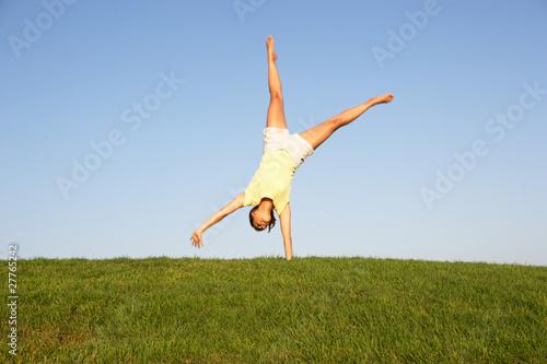 Stampa su Tela  Young woman cartwheels in field