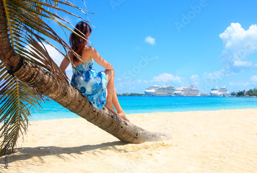 woman on a palm tree facing cruise ships in the caribbean
