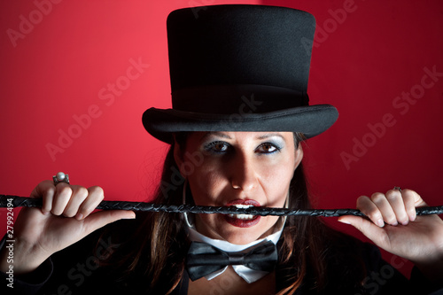 Woman in top hat biting whip Canvas Print