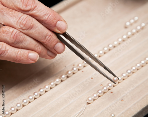 Close hand jeweler stringing pearls on a necklace