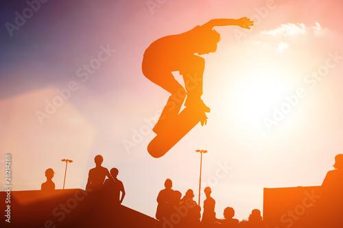 Fotografie, Obraz  Skateboarder jump over sunny sunset sky