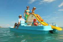 Happy Family With Boy And Girl On Pedal Boat With Yellow Slide