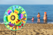 Pinwheel Toy With Flower On Beach, Family Standing In Sea