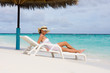 Lady relaxing in the chaise lounge on a exotic resort