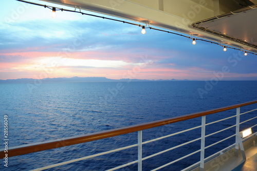 Photo  view from deck of cruise ship. sunset. row of lamps.