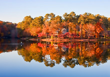 Fisherman On Calm Lake By Home In Autumn Paint