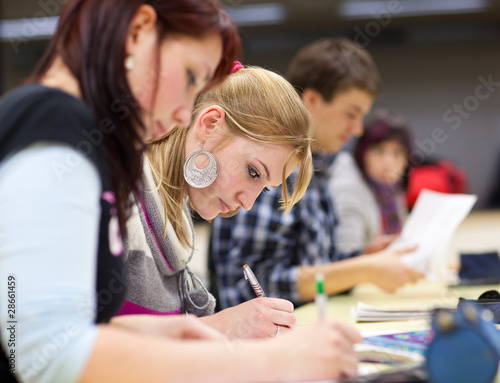 Fotografia  pretty female college student sitting in a classroom full of stu