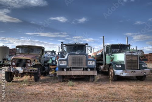 Tuinposter Oude auto s Three trucks on Junkyard