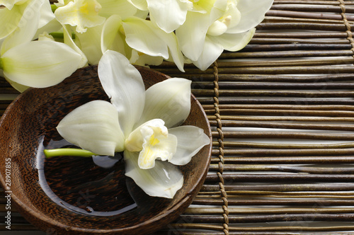 Fotobehang Spa bowl of candle and orchid on bamboo mat