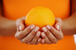 orange in woman hands