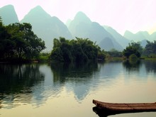 A Raft And Mountain On Yu Long River In Yangshou, China