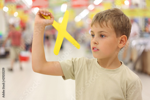 little boy holding yellow boomerang toy, standing in shop Wallpaper Mural