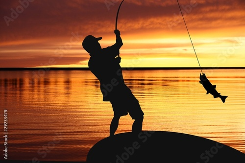 Fisherman with fishing tackle and catching fish at sunrise