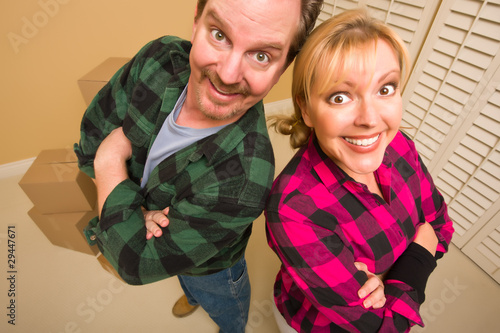 Photo  Proud Goofy Couple and Moving Boxes in Empty Room