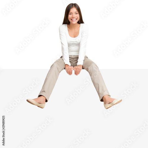 Woman sitting on billboard sign edge