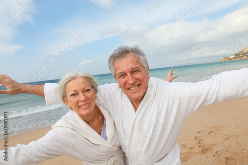 Canvas Print Senior couple in bathrobe at the beach