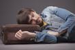 man sleeping on suitcase