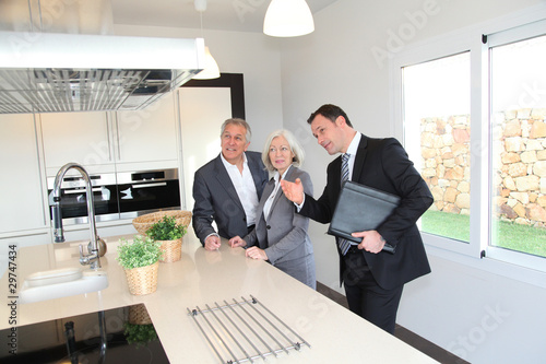 Real-estate agent showing interior of house to senior couple Canvas Print