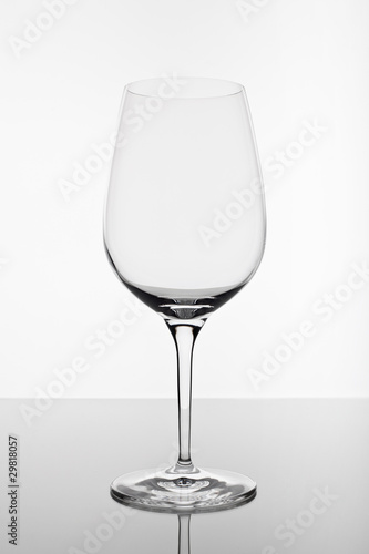 Foto op Canvas Alcohol empty wine glass with reflection on white