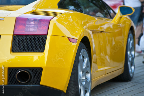 In de dag Snelle auto s Yellow sportcar, half, back, on road