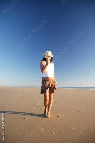 Fototapeta front woman with hat walking at beach obraz na płótnie