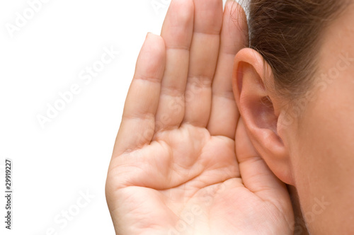 Photo Girl listening with her hand on an ear
