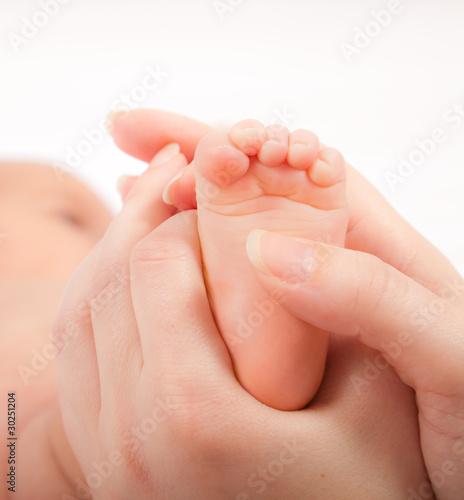 Mother's hands massaging little baby's foot