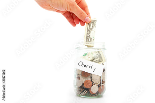 Photo  hand putting a dollar into a jar - charity donation