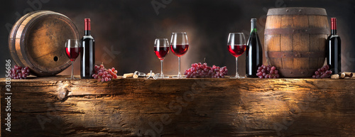 Foto op Canvas Wijn still life with red wine with barrel on old wood