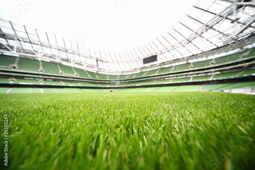 Stickers pour porte Stade de football green-cut grass in large stadium at summer day
