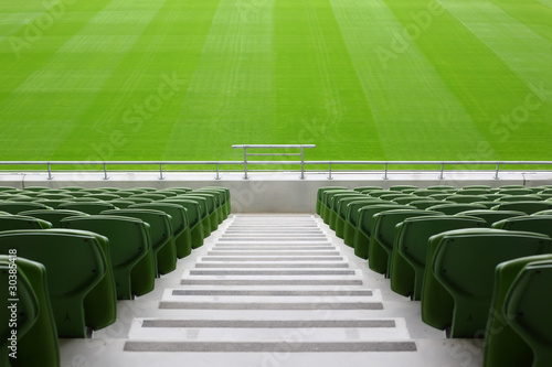 Fotobehang Stadion Rows of folded, green, plastic seats in very big, empty stadium