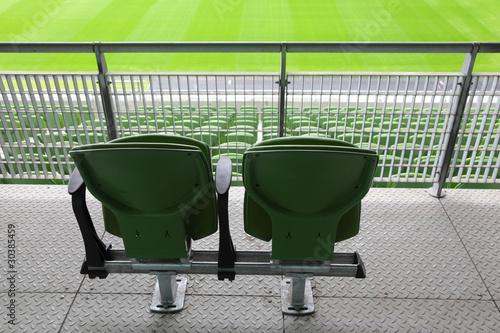Foto op Plexiglas Stadion Two green plastic seats on tribune of large stadium