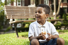 Young Boy Eating At A Park