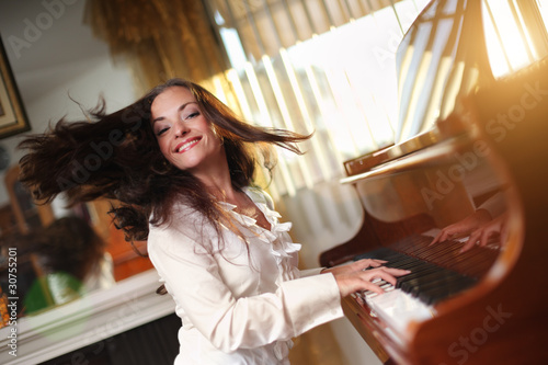 Fotografie, Obraz  Pianist. Happy young woman playing piano indoors.