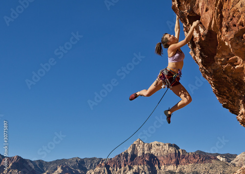 Fototapeta Female rock climber clinging to a cliff.
