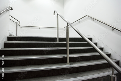Photo Stands Stairs wide staircase with chrome handrails and gray steps, white walls