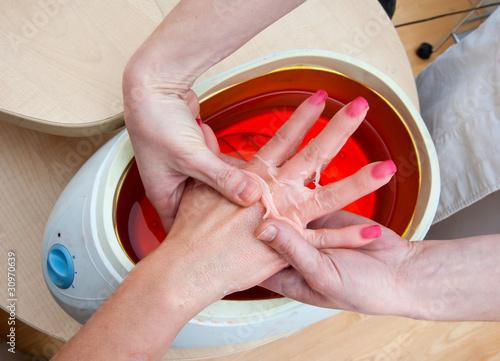 Obraz na plátně woman hand in paraffin bath