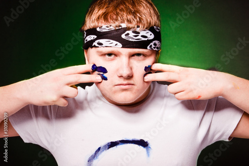 Fotografía  Young caucasian man drawing strips on face with blue paint