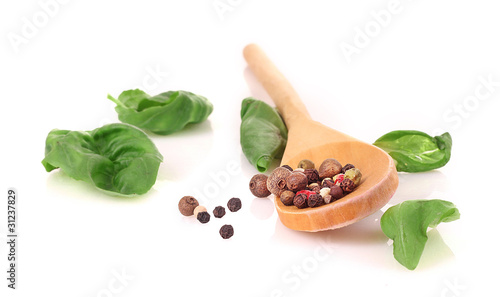 Wooden spoon, basil and spices isolated on white