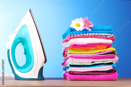 Fotografia Pile of colorful clothes and electric iron  on blue background
