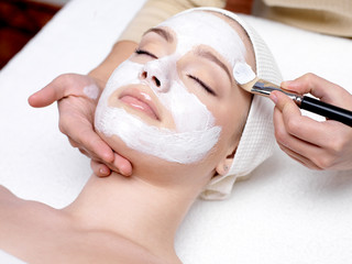 Obraz na Plexi Woman receiving facial mask at beauty salon