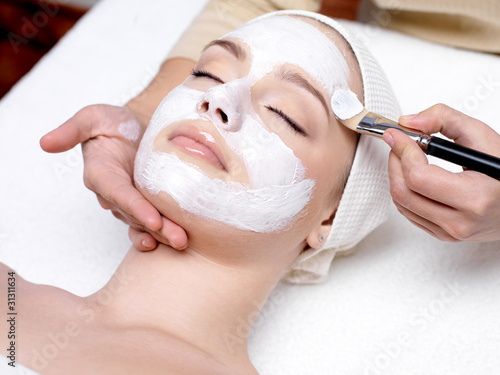 Fototapeta Woman receiving facial mask at beauty salon obraz