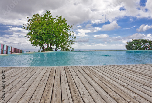 Deurstickers Tropical strand piscine avec plage terrasse en lames de deck en bois massif