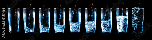 Set of glasses with water and ice on a black background