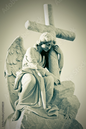 Grunge image of a sad angel holding a cross in greenish shades - 31514839