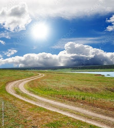 Wall Murals Blue sun and clouds over dirty road