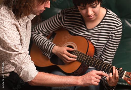 Fotografie, Obraz  Mladý hudebník učí ženský student se hrát na kytaru