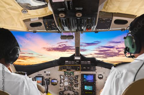 Fotografie, Obraz  Pilots in the plane cockpit and sunset