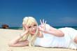 白い砂浜に横になり寛ぐ笑顔の女性